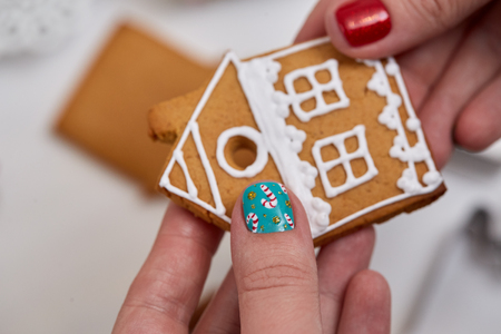 christmas manicure: Female hand with festive  Christmas manicure  holding tasty gingerbread cookie. Christmas and New Year. Stock Photo