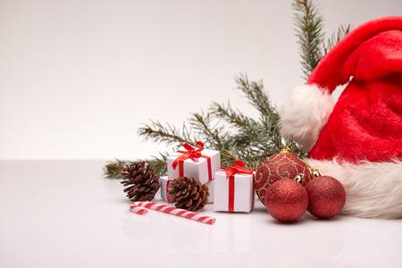 Sombrero de Papá Noel, rama de árbol de abeto con la decoración, cajas de regalo en un fondo blanco. Año nuevo y fondo de Navidad con espacio de copia de texto. Tarjeta de felicitación. Foto de archivo - 67782741