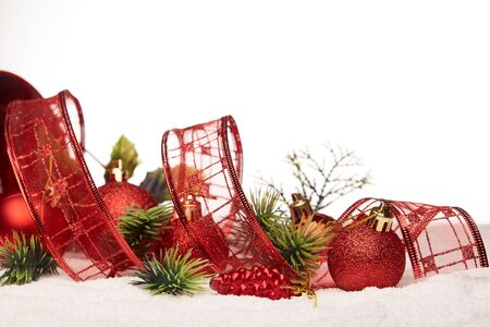 aon: Christmas decoration with red tape, fir branches, red balls  lying on snow on aon a white background. New year and Christmas background with copy space for text. Greeting card.
