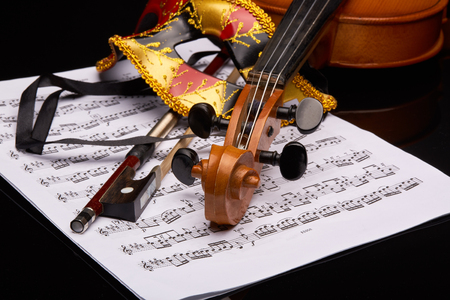musical score: Violin (fiddle) and theater mask lying on the sheet of music on a black background. String instrument.
