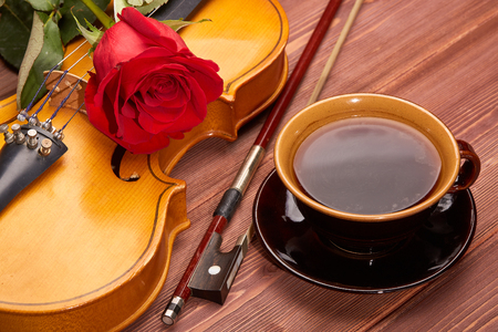 Violin (fiddle), red rose and cup of coffee on a wooden background. String instrument. Stock Photo