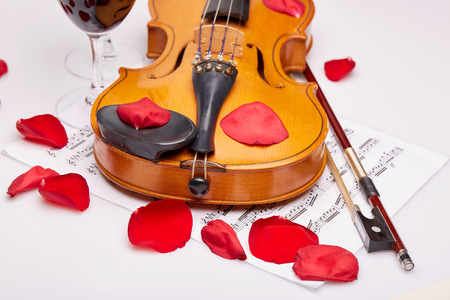 musical score: Violin (fiddle), notes, two glasses of red wine and petals of red rose on a white background. String instrument. Stock Photo
