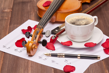 Violin, blank of a paper sheet for note, fountain pen and petals of red rose on a wooden background. Stock Photo