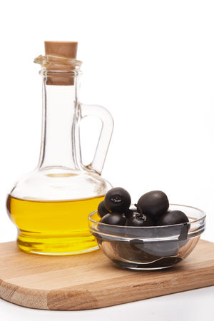 cruet: Glass cruet with Extra virgin olive oil, canned black olives in bowl stand on a wooden cutting board on a white background.