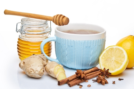 Honey in glass pot  and blue cup of tea with ginger, cinnamon, anise and lemon on a white background. Stock Photo