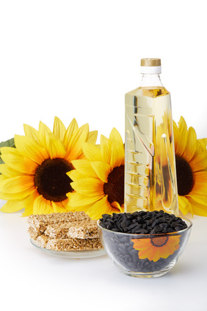 Sunflowers, seed, vegetable oil in a bottle and sweetness from pressed sunflower seeds candied in sweet syrup (sunflower seed brittle) on a white background. Sweet dessert. Harvest. Imagens