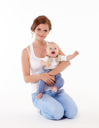 Young happy mother with sweet child sit on a white background. Happy family. Six month. photo