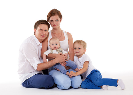 Young parents with sweet  children sit on a white background. Happy family. Six month and four years. photo