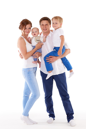 Young parents with sweet  children stand on a white background. Happy family. Six month and four years. photo