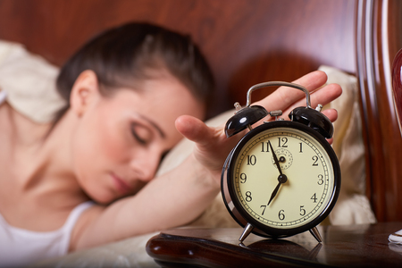 Young sleeping woman and alarm clock in the bedroom.  Selective focus on a alarm clock. Stock Photo