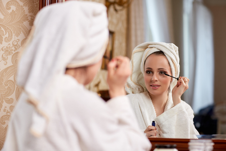 Young beautiful woman applying mascara for eyelashes sits before a house  dressing table. photo