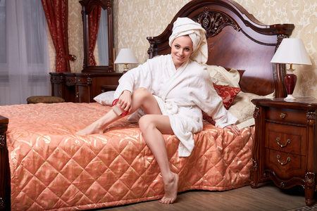 Young woman with a massager in a bedroom. Concept  of body care. photo