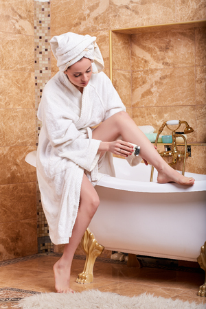Beautiful young woman shaving her legs in bathroom. Concept of body care. photo