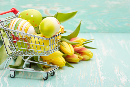 trolly: Colored easter eggs in shopping trolley and spring tulips flowers on a green wooden background.