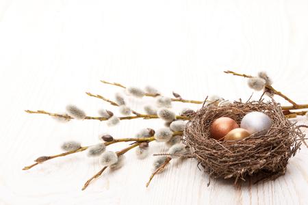 Pasen decoratie. Kwart eieren in het nest en een takken van kippenwil op een houten achtergrond. Bovenaanzicht met kopie ruimte.