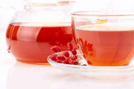 barberries: Healthy tea with barberries in glass cup on on a white background.