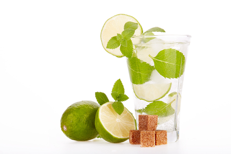 Mojito cocktail with lime, leaves of mint and pieces of sugar on a white background. Stock Photo