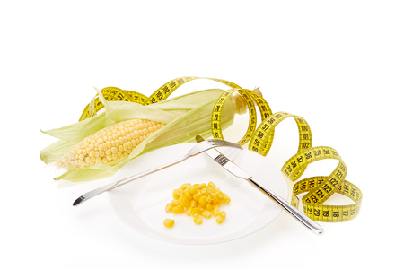 Fresh ripe ear of corn, plate with boiled corn kernels  and measuring tape on a white background. Healthy nutrition concept. Stock Photo