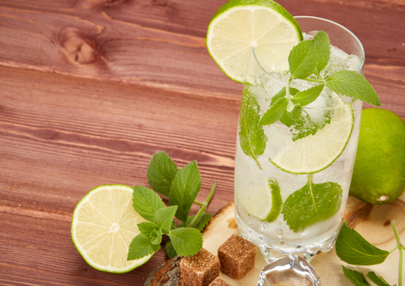 fizz: Mojito cocktail with lime, leaves of mint and pieces of sugar on a wooden background.
