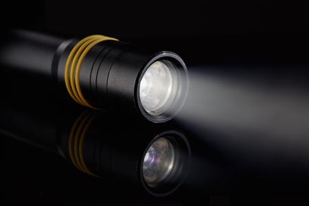 Linterna de LED metálica negra con la luz del rayo en un fondo negro.