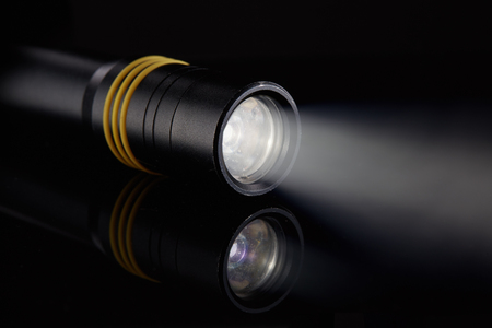 Schwarze metallische LED-Taschenlampe mit Strahlnlicht auf einem schwarzen Hintergrund.