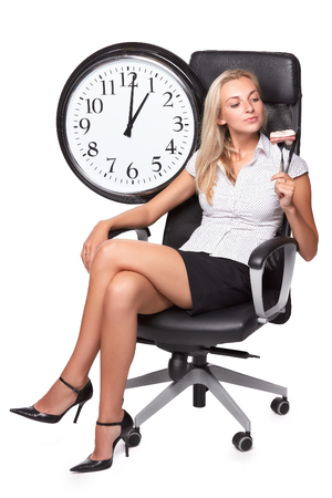 Businesswoman with knife and fork in an armchair on a white background. Lunch time.