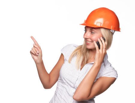 Female architect in a hard hat talks by a mobile phone on a white background.