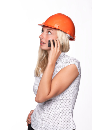 Female architect in a hard hat talks by a mobile phone on a white background. photo