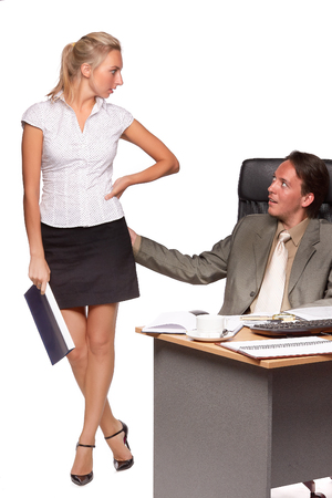 Sexual harassment in the office workplace. Businessman sitting in the office touches female colleague body.