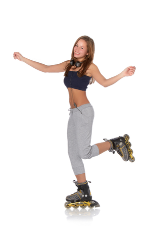 roller: The beautiful girl with earphones in rollerskates on a white background. Stock Photo