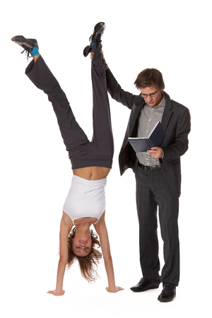 The young man with the book and the girl standing on hands on a white background. Stock Photo