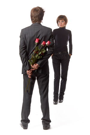 unexpectedness: The young enamoured man with flowers and his girlfriend on a white background.