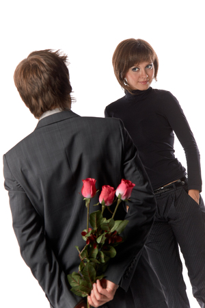 The young enamoured man with flowers and his girlfriend on a white background. photo