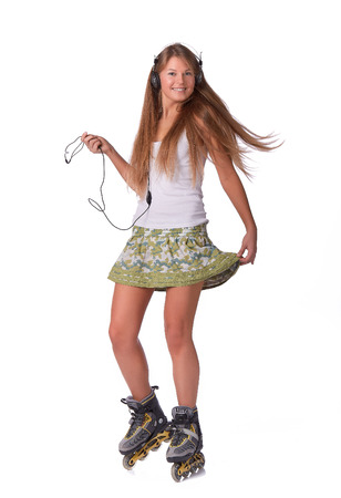 The beautiful girl with earphones in rollerskates on a white background. Stock Photo