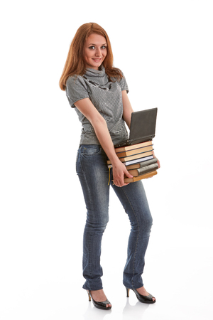 The attractive student stands with the laptop and books on a white background.