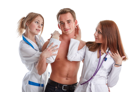 Two nurses and the young male patient on a white background.