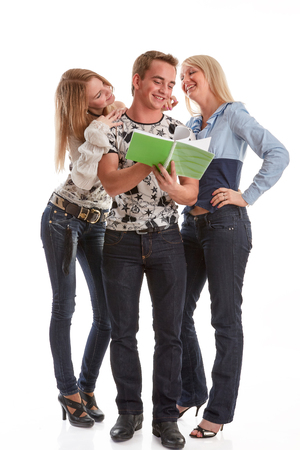 The young man and two girls with writing-books stand on a white background. Reklamní fotografie