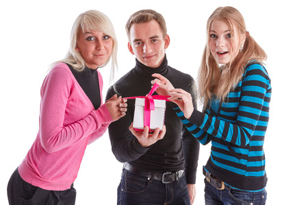 unexpectedness: Happy young people with gift box on a white background. Stock Photo