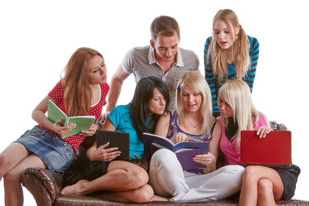 The group of young people sits on a sofa  with books and laptop  on a white background. Stock Photo