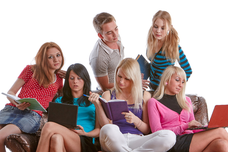 The group of young people sits on a sofa  with books and laptop  on a white background. photo