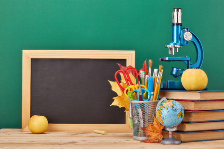 School background with stationery accessories. Books, globe, pencils and various office supplies  lying on the desk on a green background.