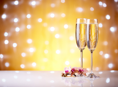 Two glasses with champange and flowers on a yellow background with lights of garland. Stock Photo