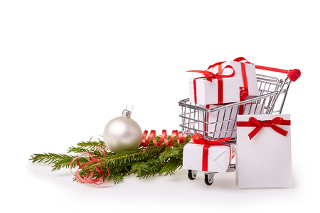 pushcart: Shopping trolley with gift boxes and brenches of fir-tree with decoration on a white background. Christmas and New Year sale.