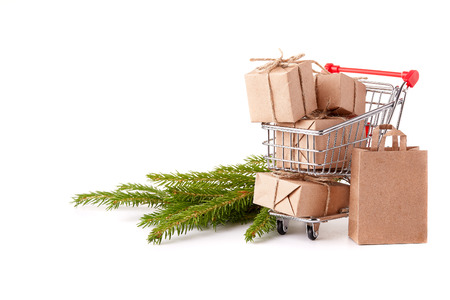 Shopping trolley with gift boxes and brenches of fir-tree on a white background. Christmas and New Year sale. Stock Photo