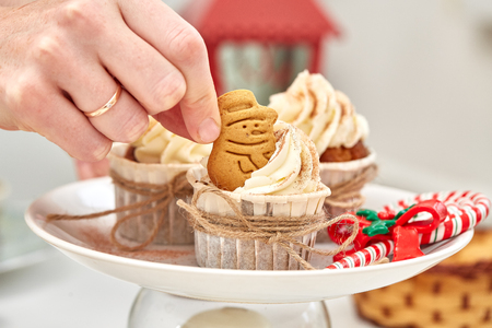 Christmas Treats. Handmade cookies, cupcakes, confection standing on the table.  Female hands decorating cupcakes using gingerbreads. Christmas and New Year. Stock Photo