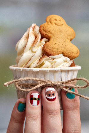 Female hand with festive  Christmas manicure  holding tasty cupcake. Christmas and New Year treat. Stock Photo