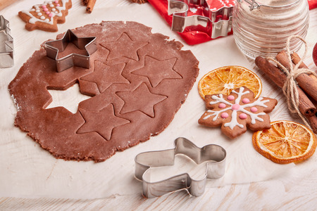 pastry cutters: Decorating gingerbreads. Dough, rolling pin, shape cutter for handmade cookies, confection lying on the wooden background. Christmas and New Year treats.