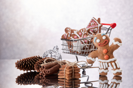 Shopping trolley with gingerbread cookies and christmas decorations standing on a grey background with reflection. Christmas and New Year sale.