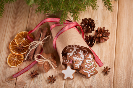 cornet: Christmas gingerbreads. Christmas decorations. Handmade cookies in paper cone  lying on the wooden background.  Top view. Christmas and New Year treats.