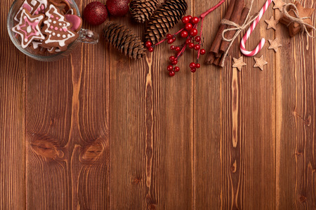 card making: Christmas decor with gingerbreads on a wooden background with copy space for text. Top view. For greeting card.